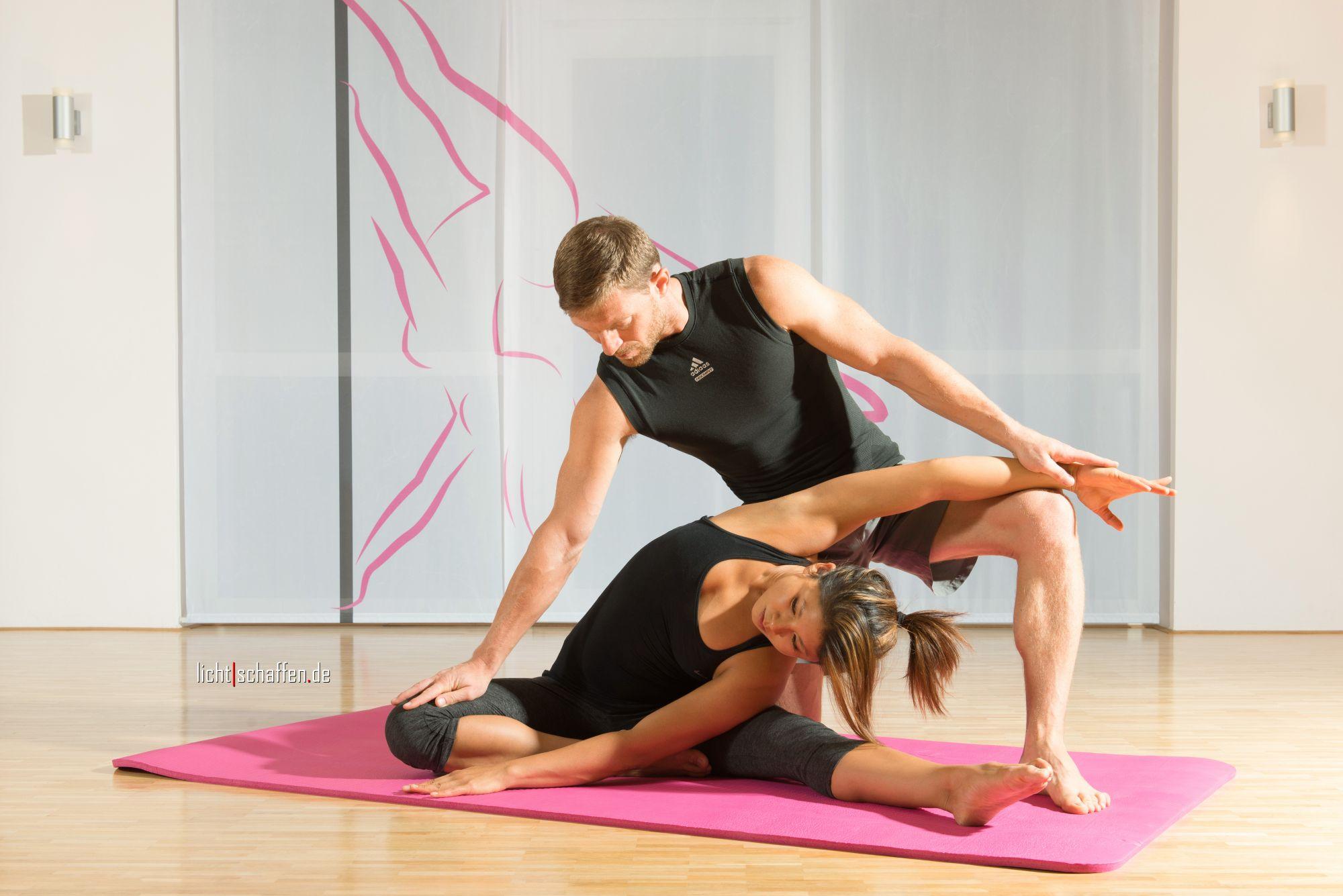 zwei Personen machen Dehnübungen bei einer Poledance Privatstunde