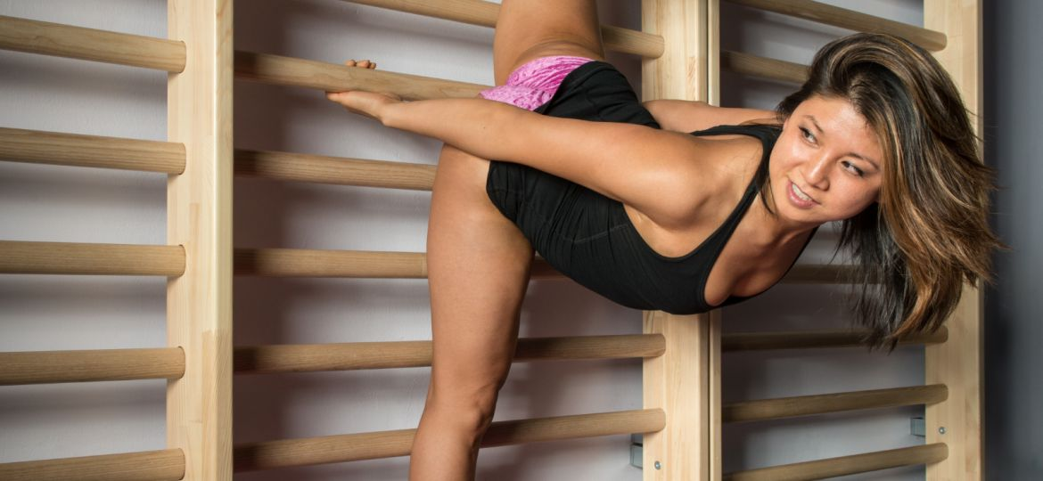 Poledance instructor does a stretching exercise on the wall bars